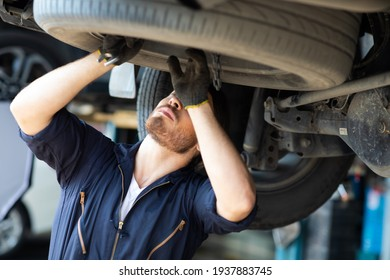 Hipster man mechanic working Under a Vehicle in a Car Service station. Expertise mechanic working in automobile repair garage.