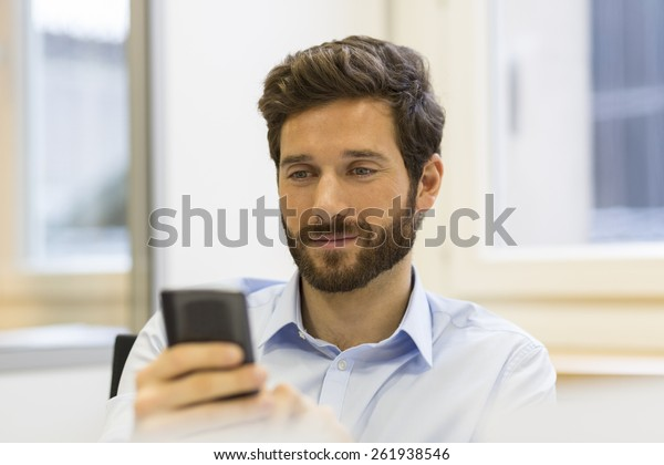 Hipster man in office. Typing text message on mobile phone