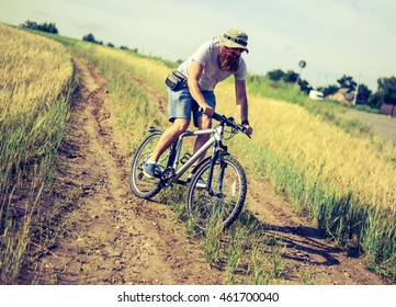 hipster man on a bicycle in the countryside