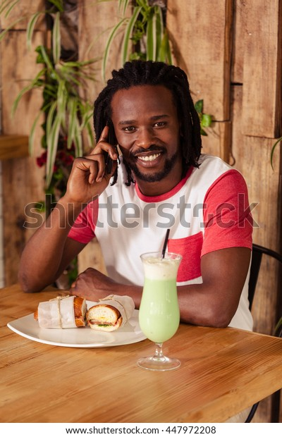 Hipster man on the phone while eating at coffee shop