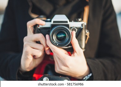 Hipster man photographer taking photo with retro camera