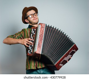 hipster man plays on the bayan, wearing a hat and glasses, isolated on a gray background