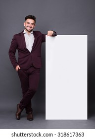 Hipster man posing with blank poster over dark grey background. Man in dark red business suit smiling for the camera.
