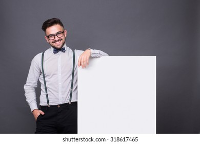 Hipster man posing with blank poster and keeping his hand in pocket. Happy man smiling for the camera over grey background.