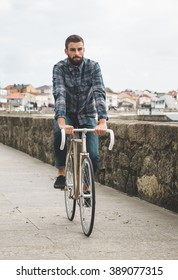 Hipster man riding in a fixie bike in the city.