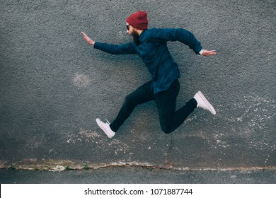 hipster man runs in the air along an empty wall. Crazy emotions. Fashionable guy with a beard