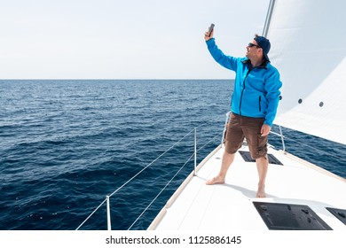 Hipster Man sailing with sails out on a sunny day and making selfie