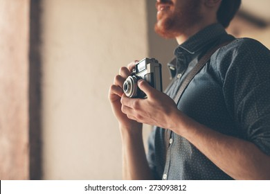 Hipster man searching for an interesting subject for his photo shooting and holding a vintage camera