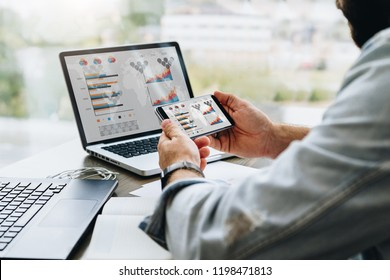 Hipster man sits in cafe, uses smartphone, works on two laptops with charts, graphs, diagrams on screen. Businessman reads an information message in phone. On table is notebook, paper documents.