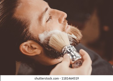 Hipster man sitting in armchair barber shop hairdresser shaves his beard with dangerous razor.