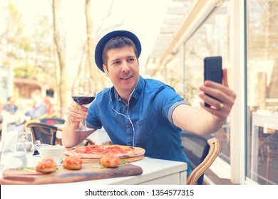 Hipster man sitting at table with large pizza and bruschetta holding glass of red wine taking selfie in city – happy tourist using mobile phone to share food with friends on social media