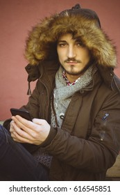 Hipster man sitting using mobile phone