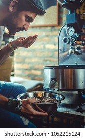 Hipster man smelling coffee beans which he roasted in a retro roaster