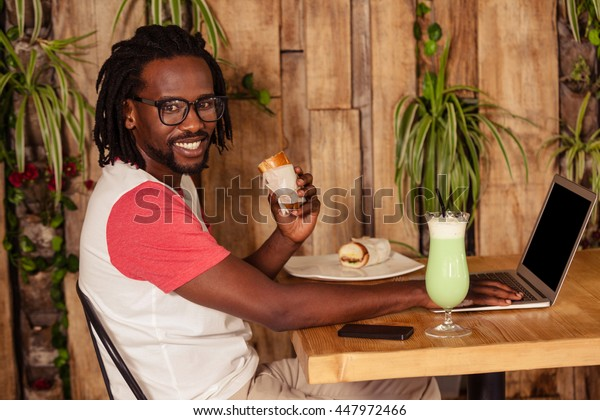 Hipster man smiling at camera while sitting at coffee shop