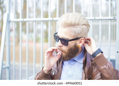 Hipster man smoking in a forbidden area in public.