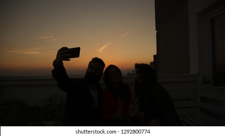 Hipster man taking picture with his smart phone with two girls at the sunset