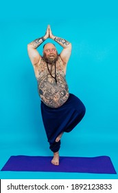 Hipster man with tattoos doing yoga and meditation exercises in the morning