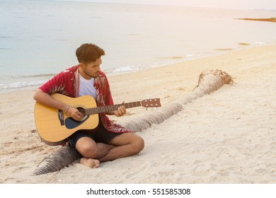 Hipster Man Teach Playing the Guitar to his Girlfriend while Sitting in the Beach look so happy. Couple in love concept.