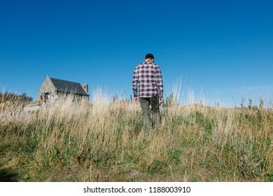 Hipster man traveller at Church of the good shepherd landmark of Lake Tekapo in sunny day, south island, New Zealand