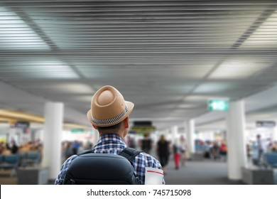 Hipster man walking in passenger terminal building  of the airport  calling on board ,travel concept.