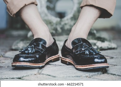 hipster man wear fashion shoes tassel loafer.sit cross-legged.stylish men shoes concept.