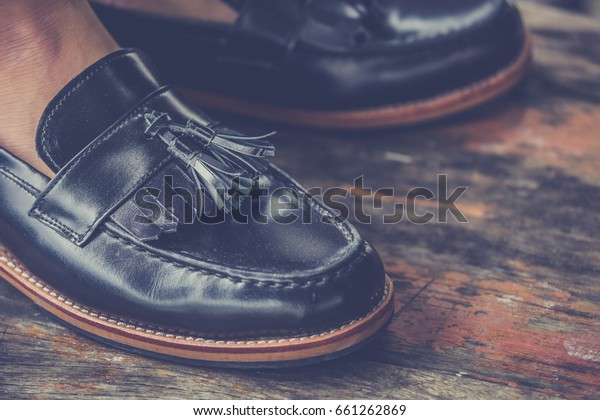 hipster man wear fashion shoes tassel loafer.on old wooden floor.stylish men shoes concept.