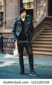 Hipster man wearing black style leather outfit with hat, pants, jacket and shoes standing on city street