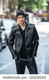 Hipster man wearing black style leather outfit with hat, pants, jacket and t-shirt standing on city street