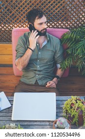 Hipster man working on laptop and using mobile phone while sitting on terrace of cafe. Attractive bearded man calling to friends.Vertical