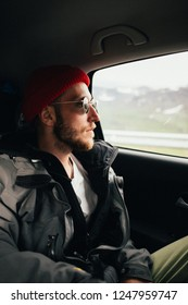 Hipster millennial adventure seeking young handsome man looks out of window of passenger seat in car. Amazing romantic roadtrip getaway, wanderlust concept of travel blogger