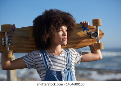hipster millennial holding longboard looking out at the ocean