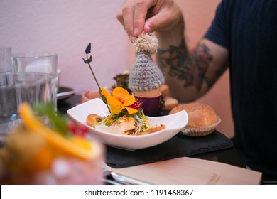Hipster millennial young man with authentic tattoos enjoys breakfast or brunch at fancy cafe or restaurant, elaborated tasting plate, decorated with edible flowers and knitted egg hat