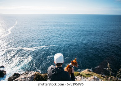 Hipster millennial young man in hoodie sweatshirt and five panel cap sits on cliff and overlooks sunset over ocean together with best friend, basenji dog