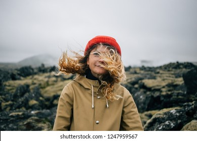 Hipster millennial young woman in raincoat and trendy beanie looks into camera. Stand in middle of epic rough iceland landscape, wind blows blond hair in face. romantic inspiration wanderlust