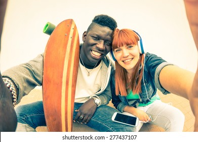 Hipster multiracial couple in love taking selfie on white background - Fun concept with alternative fashion and longboard item - Redhair girlfriend with afro american guy - Vintage filtered look