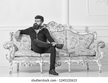 Hipster on arrogant face sits alone. Man with beard and mustache spends leisure in luxury living room. Rich and lonely concept. Owner of luxury apartment sits on sofa, white wall background.