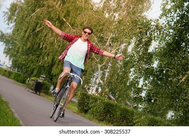 Hipster on bike at the city with no hands.