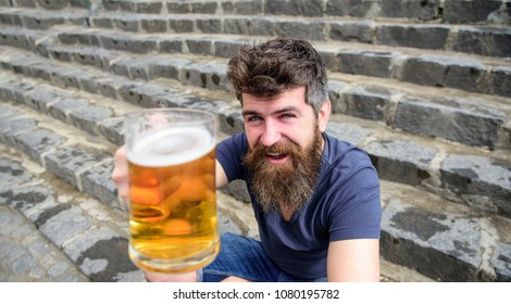 Hipster on cheerful face drinks beer outdoor. Celebration concept. Guy raising up glass with draught beer. Man with beard and mustache holds glass with beer while sits on stone stairs, defocused.