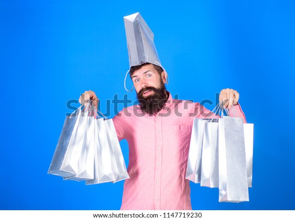 Hipster on smiling face with bag on head is addicted shopaholic. Shopping concept. Guy shopping on sales season with discounts. Man with beard and mustache carries shopping bags, blue background.