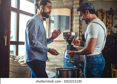 Hipster owners looking at coffee bean by the coffee roaster machine