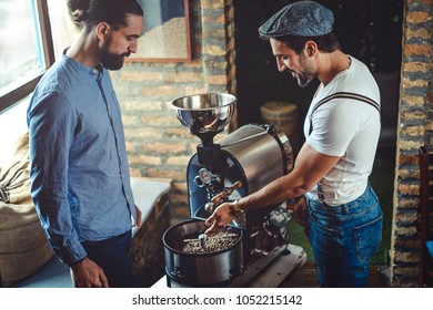 Hipster owners looking at the  coffee roaster machine