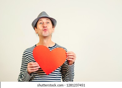 Hipster with paper red heart. Air kiss and love. Funny happy man holds symbols of Valentine's day. Kiss, flirt, gift, feelings concept. Happy Valentine day. Full of love. Happy boyfriend send air kiss