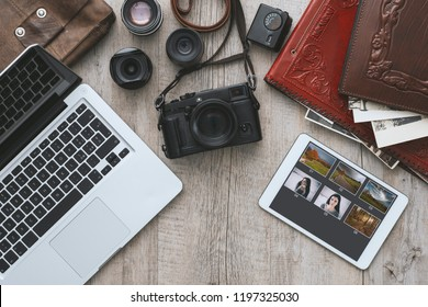 Hipster photography equipment with laptop and digital tablet on a vintage wooden desktop, flat lay