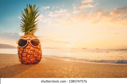 Hipster pineapple with sunglasses on a sandy at tropical beach.