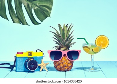 Hipster Pineapple in Trendy Sunglasses, Cocktail on Beach. Tropical Fruit. Bright Summer Color. Minimal Art. Fun party Mood. Retro Design camera