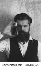 Hipster posing with bottle of red liqueur. Brutal man with long beard, moustache and stylish hair on beige wall. Alcohol, appetizer and aperitif. Addictive and convive. Unhealthy lifestyle. Bad habit