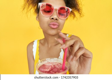 Hipster pretty millennial african teen gen z girl holding straw ice drink in hands wear pink sunglasses stylish glasses enjoy cool cocktail party isolated on yellow summer studio background. Close up.