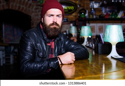 Hipster relaxing at bar. Bar is relaxing place to have drink and relax. Man with beard spend leisure in dark bar. Brutal lonely hipster. Brutal hipster bearded man sit at bar counter. Friday evening.