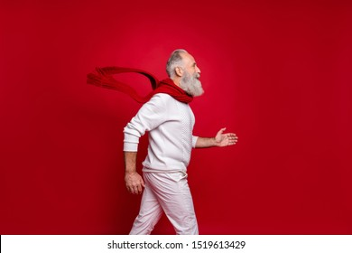Hipster senior man plays rushing santa at corporate party wearing fashion knitted clothes isolated red background