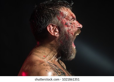 Hipster shout with bloody beard on brutal face profile. Bearded man with tattoo on chest on black background. Magic, enchantment, witchcraft. Wizard, sorcerer, warlock. Halloween holidays celebration